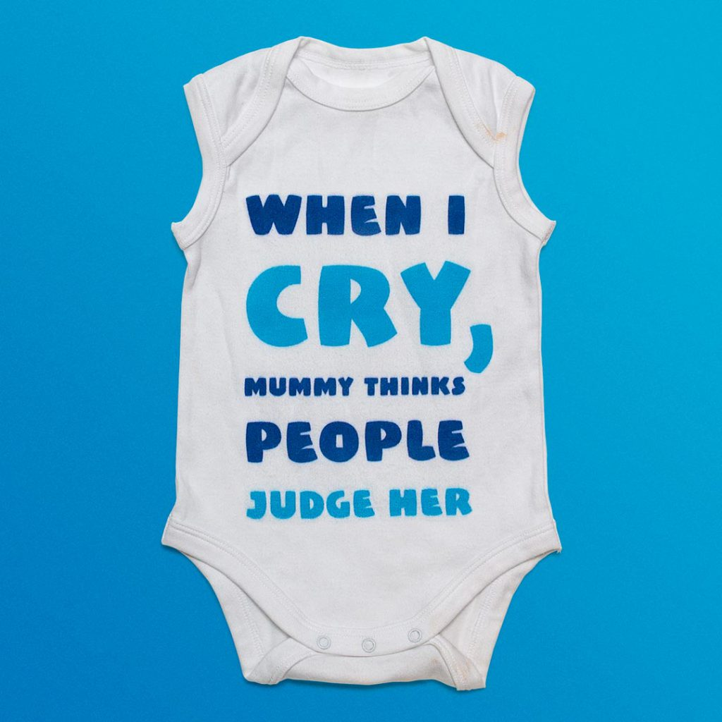 Infant's clothing with 'When I cry, mummy thinks people judge her' printed on it