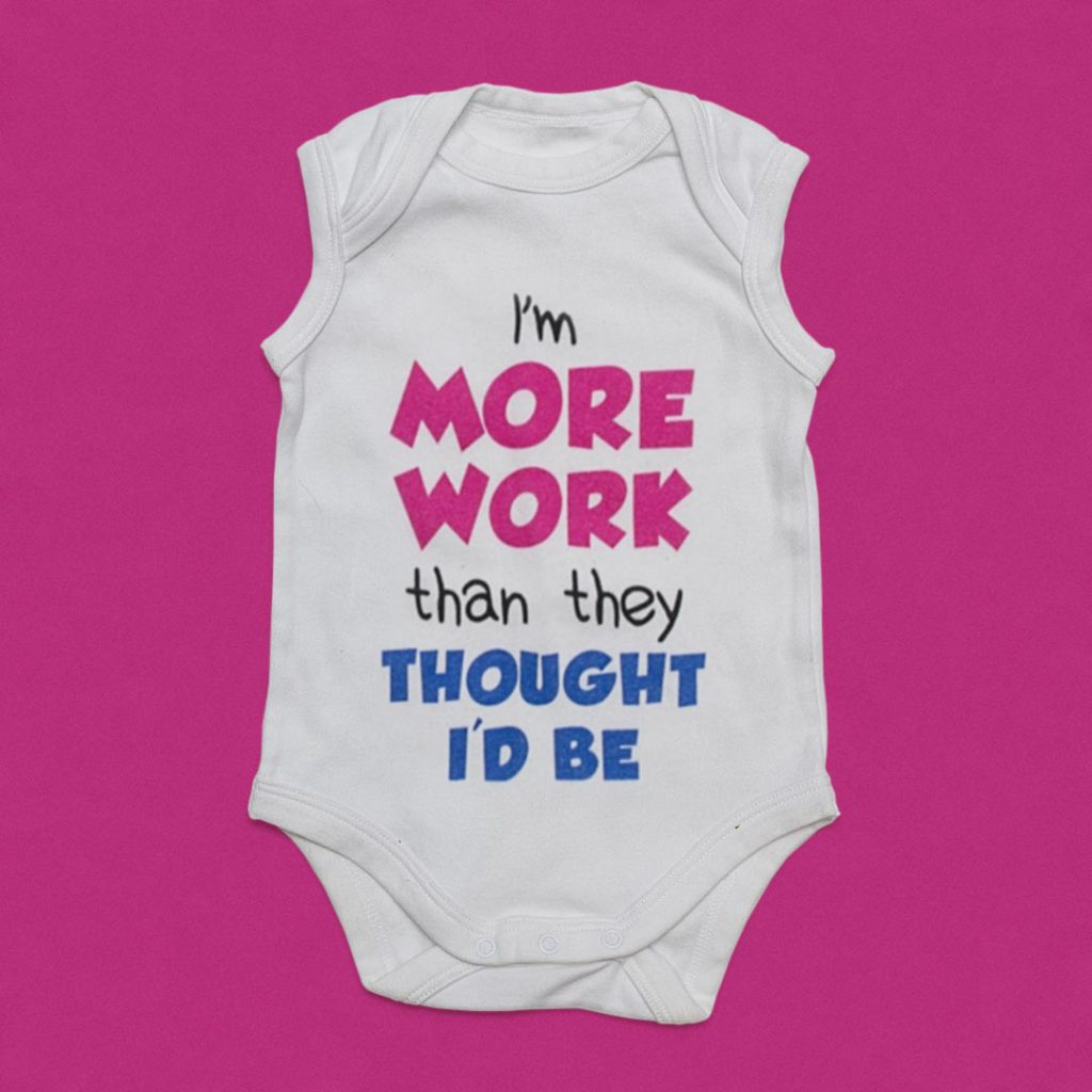 Infant's clothing with 'I'm more work than they thought I'd be' printed on it