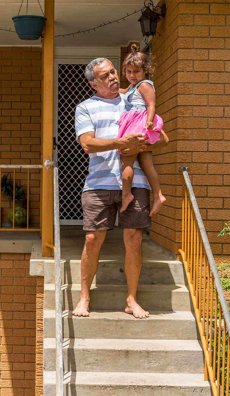 Man holding a small child on the front steps of a house