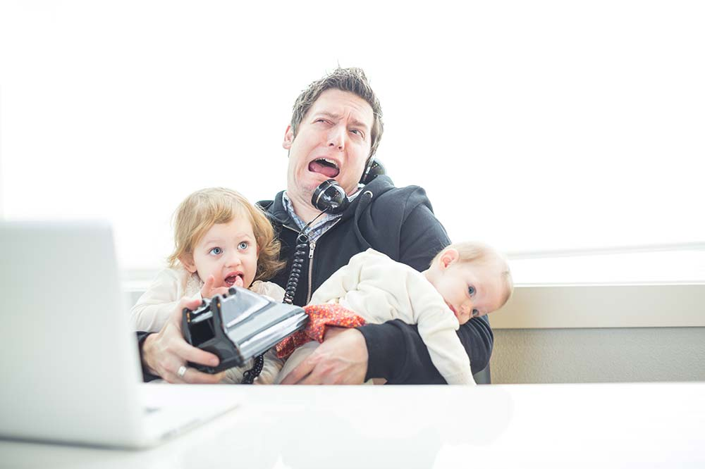A man talking on a phone, juggling two infants