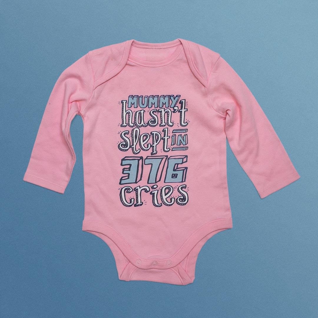 Infant's clothing with 'Mummy hasn't slept in 376 cries' printed on it