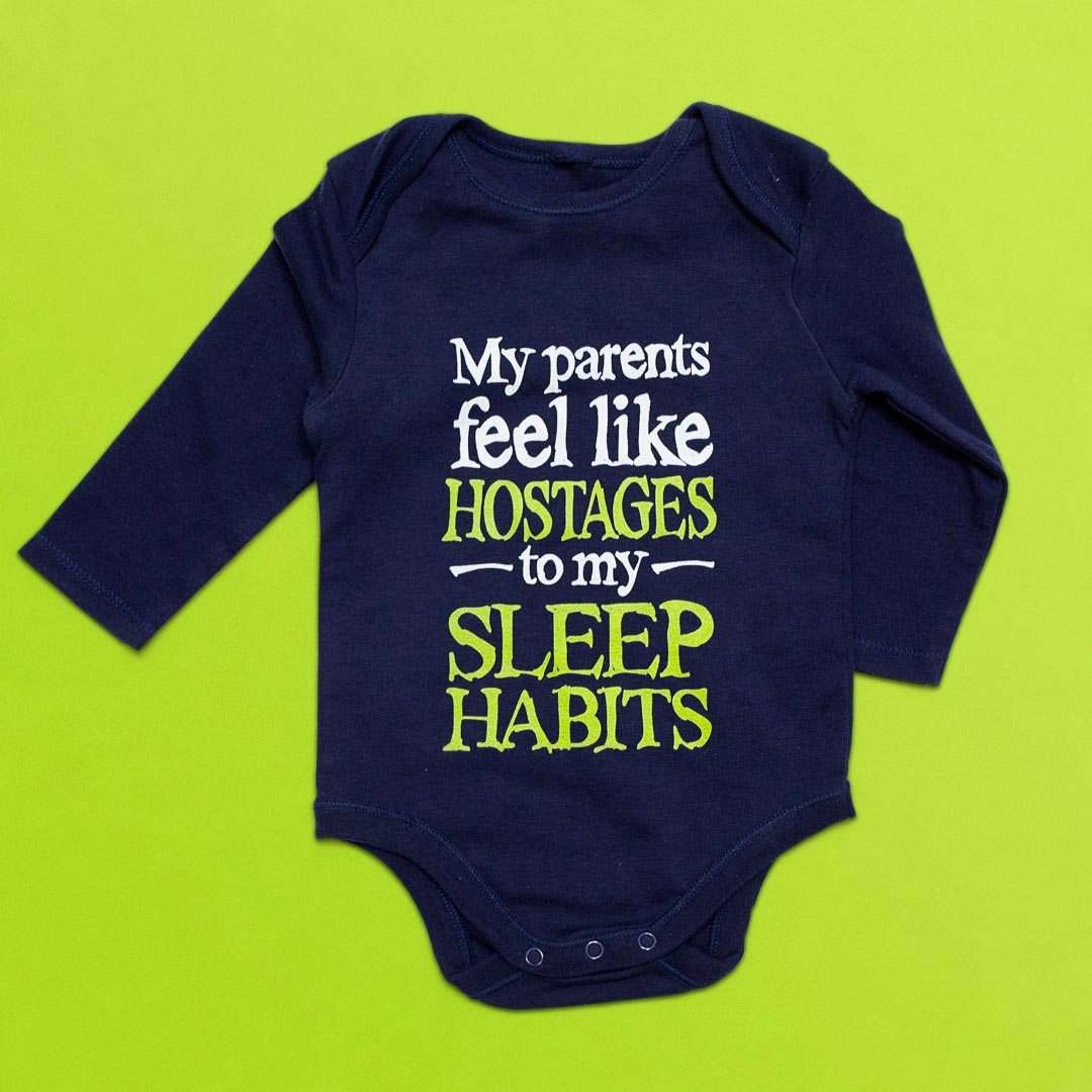 Infant's clothing with 'My parents feel like hostages to my sleep habits' printed on it