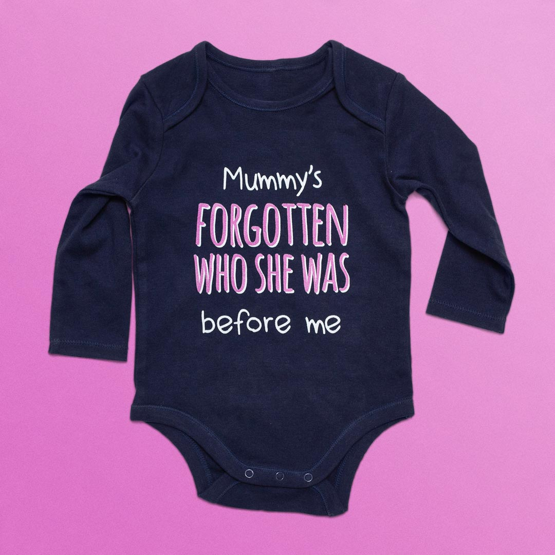 Infant's clothing with 'Mummy's forgotten who she was before me' printed on it