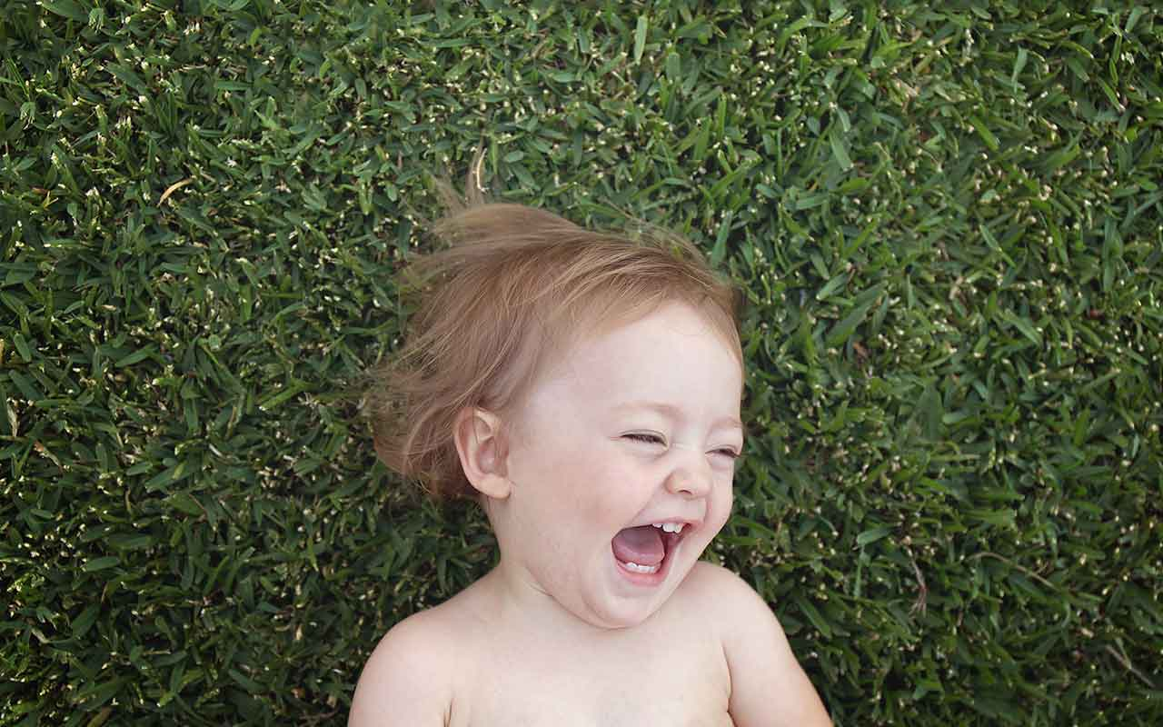 Baby laughing while lying on grass